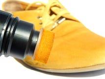 Bota amarilla y pintura amarilla para los zapatos en el fondo blanco fotos de archivo