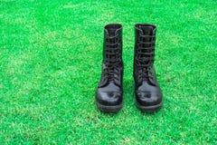 bota de combate negra en campo de hierba verde Imagen de archivo