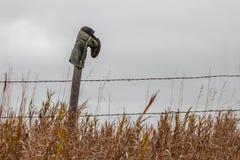 Bota de vaqueiro que pendura em um cargo da cerca Fotos de Stock