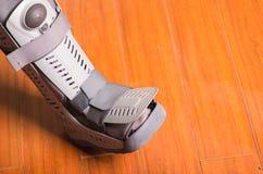 Bota gris ortopédica, cuando una cierta parte de los pies es piso afectado, de madera del fondo Imagenes de archivo