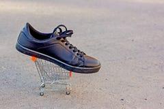 A bota preta encontra-se na cesta para produtos, espaço do brinquedo da cópia imagem de stock
