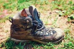 Bota que camina sucia en prado verde Fotografía de archivo libre de regalías