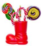 Bota roja de Santa Claus, zapato con las piruletas dulces coloreadas, candys Bota de San Nicolás con los regalos de los presentes Imagen de archivo