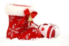 A bota vermelha de Santa com as quinquilharias na neve imagem de stock royalty free