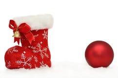 A bota vermelha de Santa com uma quinquilharia na neve no branco imagens de stock royalty free