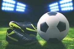 Bota y balón de fútbol en el campo Imágenes de archivo libres de regalías
