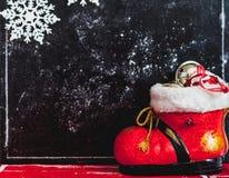 Bota y copos de nieve del Año Nuevo en fondo oscuro Foto de archivo libre de regalías