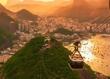Botafogo, mountain Urca and cable car to mountain Urca and cable car to mountain Sugar Loaf in Rio de Janeiro. Brazil. Sunset view of Botafogo, mountain Urca and royalty free stock photos