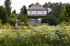 Botanic garden-munich. Café with terrace and blue sunshades in the botanic garden of munich. The café is surrounded by an romantic arrangement of green trees Stock Photo