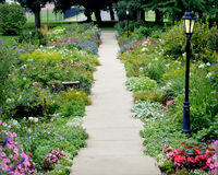 Botanical Garden Path with Lamposts. A flower garden at Saint John& x27;s chapel in Racine, Wisconsin that goes on both sides of the path leading out from the Royalty Free Stock Images