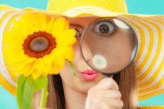 Botanist woman with sunflower and magnifying glass. Botanist woman funny face expression in yellow hat examining flower looking through magnifying glass on blue Stock Photo
