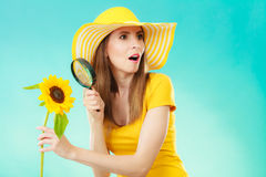 Botanist woman with sunflower and magnifying glass. Botanist woman funny face expression in yellow hat examining flower looking through magnifying glass on blue Stock Images