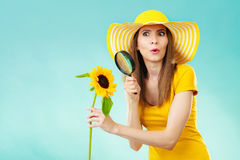Botanist woman with sunflower and magnifying glass. Botanist woman surprised face expression in yellow hat examining flower looking through magnifying glass on Royalty Free Stock Image