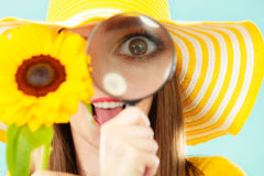 Botanist woman with sunflower and magnifying glass. Botanist woman surprised face expression in yellow hat examining flower looking through magnifying glass on Stock Photo