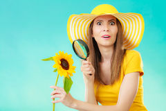 Botanist woman with sunflower and magnifying glass Stock Images