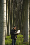 Botanist working outdoors. Botanist working with laptop inside a poplar wood Royalty Free Stock Image