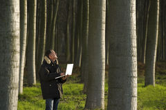 Botanist working outdoors. Botanist working with laptop inside a poplar wood Royalty Free Stock Images