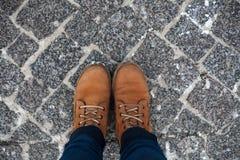 Botas amarillas en un camino de piedra en invierno fotos de archivo libres de regalías