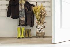 Botas chuvosas das crianças, revestimentos marrons, lenço e um vaso com f secado fotografia de stock royalty free