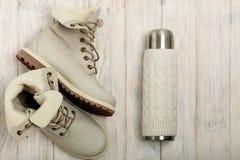 Botas claras do inverno e uma garrafa térmica na tampa feita malha no bri Foto de Stock Royalty Free