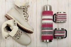Botas claras do inverno e uma garrafa térmica na tampa feita malha no bri Fotos de Stock Royalty Free