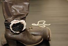 Botas con clase de Brown con la pulsera y las perlas Fotos de archivo libres de regalías