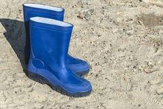 Botas de borracha azuis na praia imagens de stock