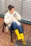 Botas de borracha bebendo do outono do chá da mulher alegre Fotografia de Stock