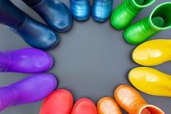 Botas de borracha coloridas de todas as cores do suporte arco-íris-vermelho, alaranjado, amarelo, verde, azul, ciano e roxo na su foto de stock