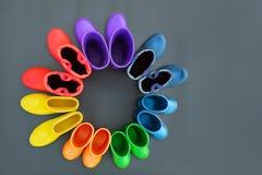 Botas de borracha coloridas de todas as cores do suporte arco-íris-vermelho, alaranjado, amarelo, verde, azul, ciano e roxo na su fotografia de stock