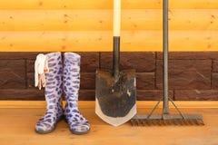 Botas de borracha com pá e ancinho Imagem de Stock
