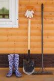 Botas de borracha com pá e ancinho Fotografia de Stock Royalty Free