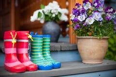 Botas de borracha e flores Imagens de Stock Royalty Free