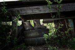 Botas de borracha velhas em pneus Fotos de Stock Royalty Free