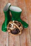 Botas de borracha verdes e uma cesta completamente dos cogumelos em um fundo de madeira Fotografia de Stock Royalty Free
