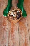 Botas de borracha verdes e uma cesta completamente dos cogumelos em um fundo de madeira Imagem de Stock