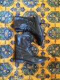 Botas de combate de cuero negras en la manta oriental fotografía de archivo libre de regalías