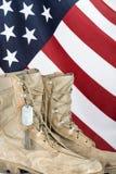 Botas de combate e etiquetas de cão velhas com bandeira americana fotos de stock