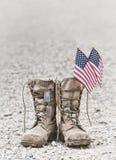 Botas de combate velhas com etiquetas de cão e as bandeiras americanas fotos de stock