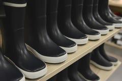 Botas de goma negras en estantes de una tienda en una tienda Imagen de archivo libre de regalías