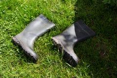 Botas de goma negras en hierba verde Imagen de archivo libre de regalías