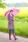 Botas de goma que llevan de la mujer con el paraguas Imagen de archivo