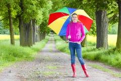 Botas de goma que llevan de la mujer con el paraguas Imagen de archivo libre de regalías