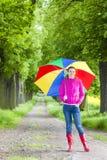 Botas de goma que llevan de la mujer con el paraguas Foto de archivo