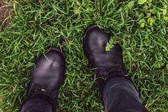 Botas de la mujer negra en hierba verde foto de archivo