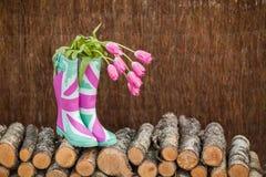 Botas de lluvia con los tulipanes frescos imagen de archivo
