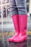Botas de lluvia de la chica joven que llevan Imagen de archivo