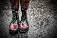Botas de lluvia rojas decorativas que llevan en la lluvia en las pavimentadoras fotos de archivo libres de regalías