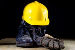 Botas de trabalho enlameadas com capacete e luvas Acessórios para imagens de stock
