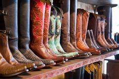 Botas de vaqueiro brilhantes brilhantes que estão em uma prateleira na loja de ofício Fotos de Stock Royalty Free